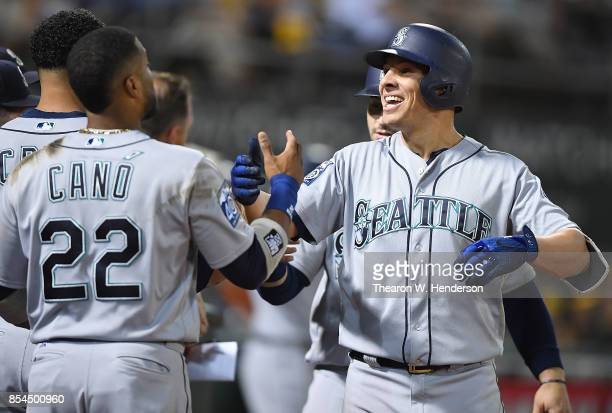 Danny Valencia and Robinson Cano of the Seattle Mariners celebrates after Valencia hit a threerun homer against the Oakland Athletics in the top of...