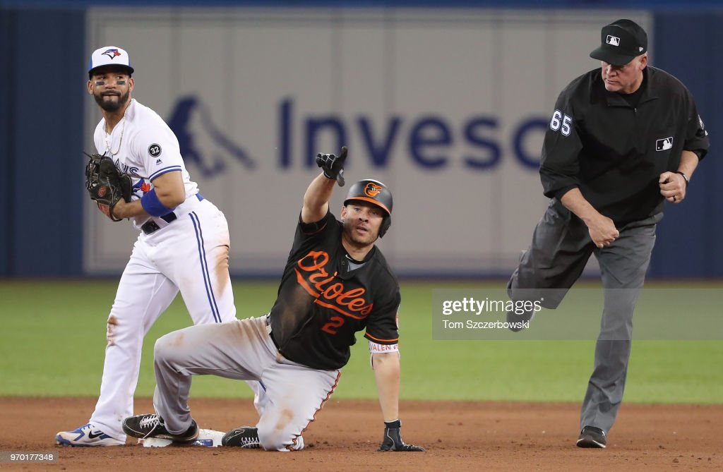 Danny Valencia #2 of the Baltimore Orioles is called out at second base after trying to stretch a single into a double by second base umpire Ted Barrett #65 and calls for a video challenge of the play in the ninth inning during MLB game action against the Toronto Blue Jays at Rogers Centre on June 8, 2018 in Toronto, Canada.