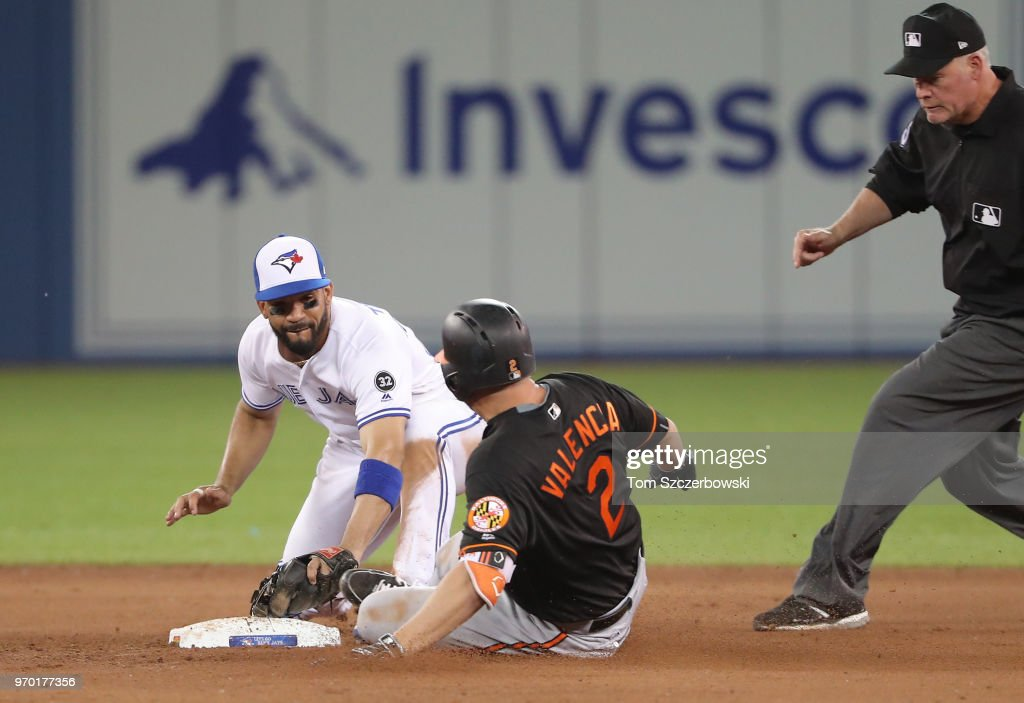 Danny Valencia #2 of the Baltimore Orioles is tagged out at second base after trying to stretch a single into a double as second base umpire Ted Barrett #65 watches in the ninth inning during MLB game action as Devon Travis #29 of the Toronto Blue Jays applies the tag at Rogers Centre on June 8, 2018 in Toronto, Canada.