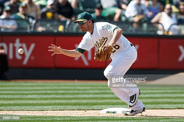 Danny Valencia of the Oakland Athletics barehands a ground ball during the ninth inning against the Detroit Tigers at the Oakland Coliseum on May 28...