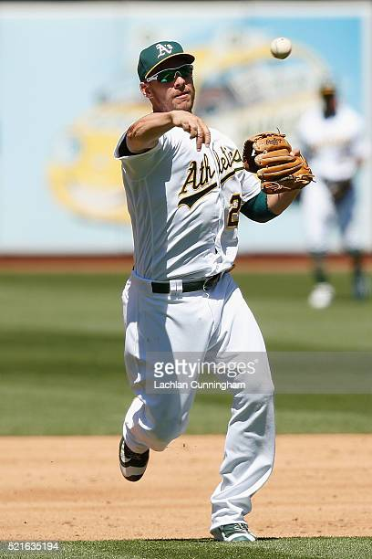 Danny Valencia of the Oakland Athletics fields the ball at third base and throws to first to get the out of Lorenzo Cain of the Kansas City Royals in...