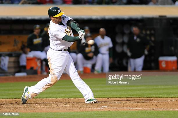 Danny Valencia of the Oakland Athletics hits an RBI single against the Texas Rangers in the fourth inning at Oco Coliseum on June 13 2016 in Oakland...