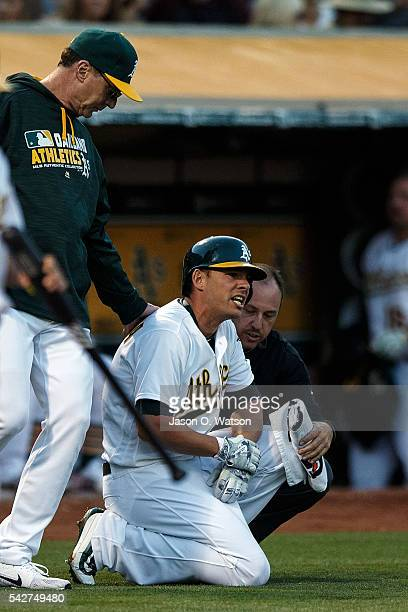 Danny Valencia of the Oakland Athletics is attended to by head athletic trainer Nick Paparesta and manager Bob Melvin after getting hit by a pitch...