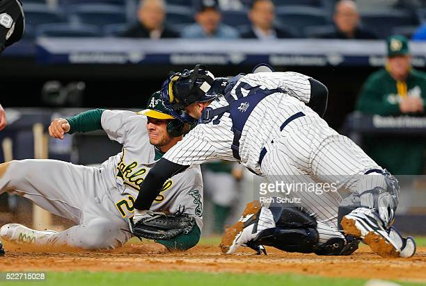 Danny Valencia of the Oakland Athletics is tagged out at the plate by catcher Brian McCann of the New York Yankees after attempting to tag up on a...