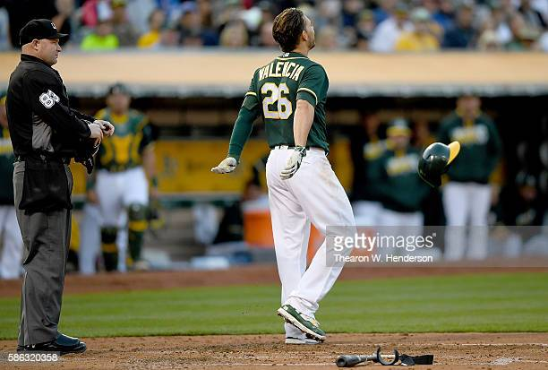 Danny Valencia of the Oakland Athletics reacts and tosses his helmet away after he was called out on strikes by home plate umpire Mike Estabrook in...