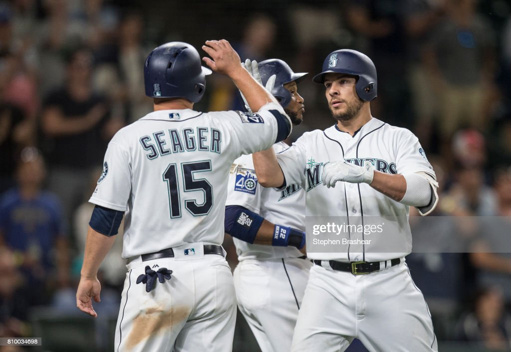 Danny Valencia #26, right, of the Seattle Mariners is congratulated by Kyle Seager #15 of the Seattle Mariners and Robinson Cano #22 of the Seattle Mariners after hitting a three-run home run off of relief pitcher Daniel Coulombe #35 of the Oakland Athletics during the ninth inning of a game at Safeco Field on July 6, 2017 in Seattle, Washington. The Athletics won 7-4.