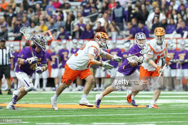 Danny Varello of the Syracuse Orange reaches for a loose ball as teammate Brett Kennedy looks on against the Albany Great Danes during the first half...