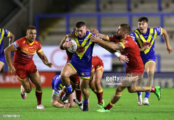 Danny Walker of Warrington Wolves is tackled by Michael McIlorum of Catalans Dragons during the Betfred Super League match between Warrington Wolves...