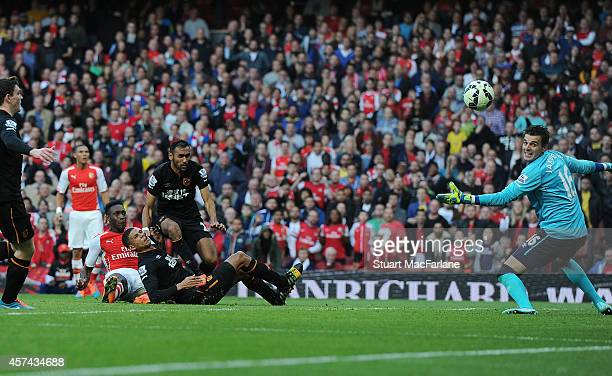 Danny Welbeck chips the ball over Hull goalkeeper Eldin Jakupovic to score the 2nd Arsenal goal during the Barclays Premier League match between...