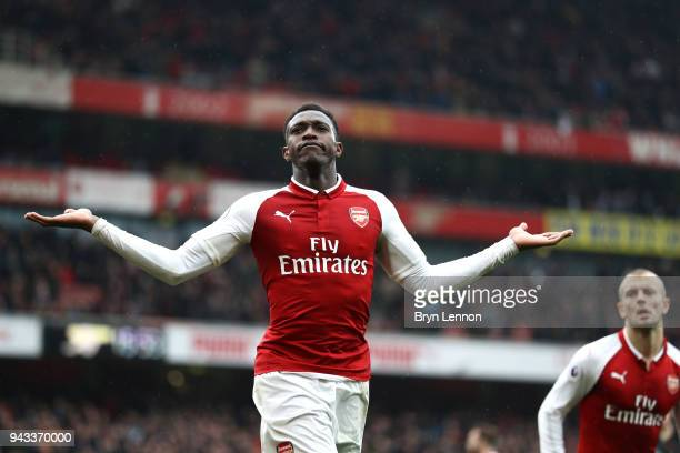 Danny Welbeck of Arsenal celebrates with team mate Jack Wilshere after scoring his sides third goal during the Premier League match between Arsenal...