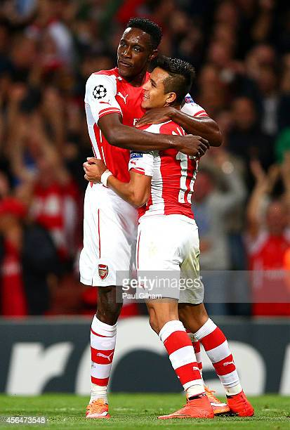 Danny Welbeck of Arsenal celebrates with teammate Alexis Sanchez after scoring the opening goal during the UEFA Champions League group D match...