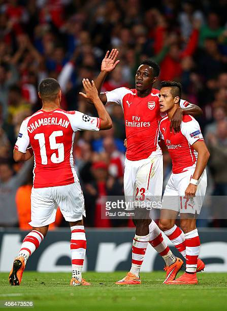 Danny Welbeck of Arsenal celebrates with teammates Alex OxladeChamberlain and Alexis Sanchez after scoring the opening goal during the UEFA Champions...