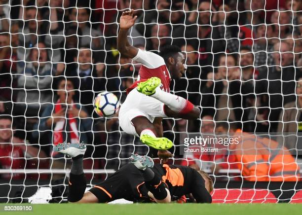 Danny Welbeck of Arsenal collides with Kasper Schmeichel of Leicester City as he scores his team's second goal during the Premier League match...