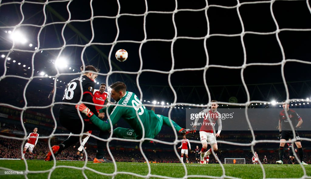 Danny Welbeck of Arsenal heads home the third goal past Gianluigi Donnarumma of AC Milan during the UEFA Europa League Round of 16 Second Leg match between Arsenal and AC Milan at Emirates Stadium on March 15, 2018 in London, England.