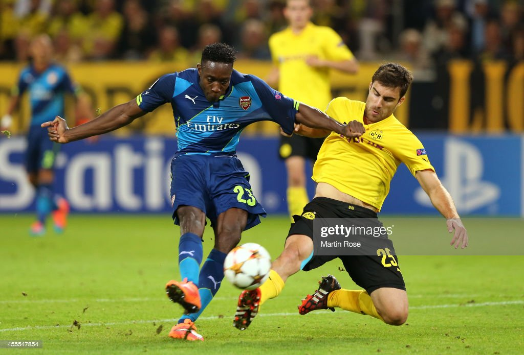 Danny Welbeck of Arsenal holds off the challenge from Sokratis Papastathopoulos of Borussia Dortmund as he takes a shot on goal during the UEFA Champions League Group D match between Borussia Dortmund and Arsenal at Signal Iduna Park on September 16, 2014 in Dortmund, Germany.