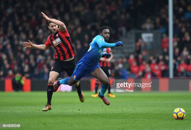 Danny Welbeck of Arsenal is tipped by Simon Francis of Bournemouth during the Premier League match between AFC Bournemouth and Arsenal at Vitality...