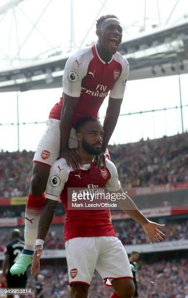 Danny Welbeck of Arsenal leaps on top of goal scorer Alexandre Lacazette of Arsenal during the Premier League match between Arsenal and West Ham...