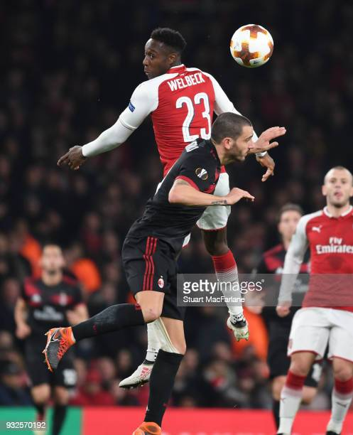 Danny Welbeck of Arsenal outjumps Milan's Leonardo Bonucci during UEFA Europa League Round of 16 match between AC Milan and Arsenal at Emirates...