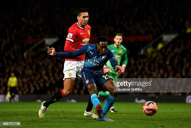 Danny Welbeck of Arsenal scores his team's second goal despite the attentions from Chris Smalling of Manchester United during the FA Cup Quarter...