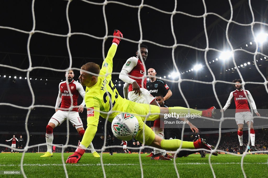 Danny Welbeck of Arsenal (23) scores their first goal past goalkeeper Joe Hart of West Ham United during the Carabao Cup Quarter-Final match between Arsenal and West Ham United at Emirates Stadium on December 19, 2017 in London, England.