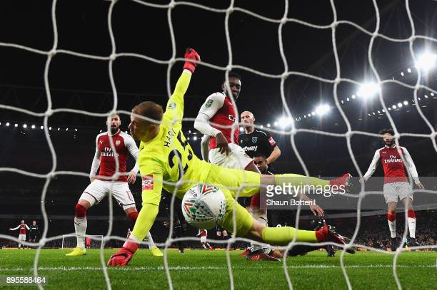 Danny Welbeck of Arsenal scores their first goal past goalkeeper Joe Hart of West Ham United during the Carabao Cup QuarterFinal match between...