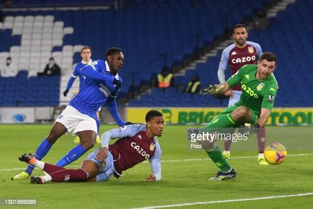 Danny Welbeck of Brighton & Hove Albion has a shot saved by Emiliano Martinez of Aston Villa whilst under pressure from Ezri Konsa of Aston Villa...