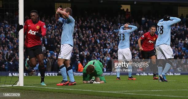 Danny Welbeck of Manchester United celebrates Robin van Persie scoring their third goal while Pablo Zabaleta Joe Hart Matija Nastasic and Kolo Toure...