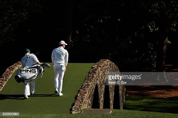Danny Willett of England and Billy Foster caddie for Lee Westwood of England walk across the Hogan bridge to the 12th green during the final round of...