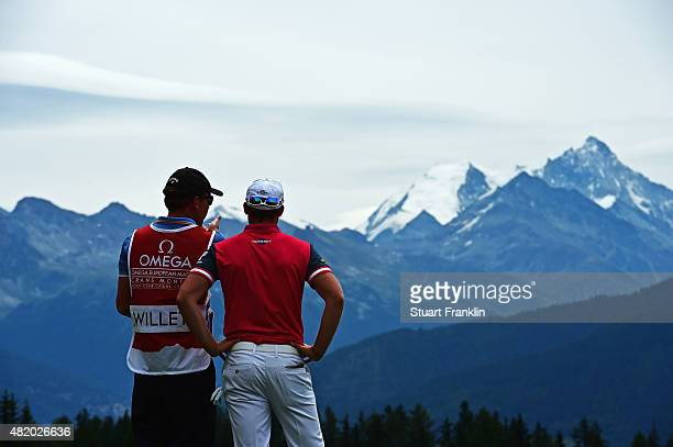 Danny Willett of England and caddie discuss a shot during the final round of the Omega European Masters at CranssurSierre Golf Club on July 26 2015...