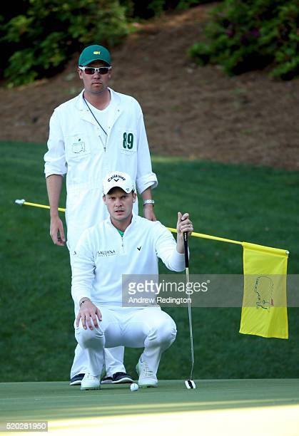 Danny Willett of England and caddie Jonathan Smart line up a putt on the 13th green during the final round of the 2016 Masters Tournament at Augusta...