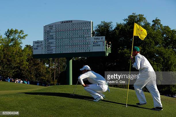 Danny Willett of England and caddie Jonathan Smart line up a putt on the 18th green during the final round of the 2016 Masters Tournament at Augusta...