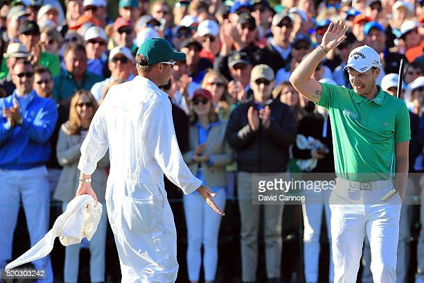 Danny Willett of England and caddie Jonathan Smart react on the 18th green after finishing during the final round of the 2016 Masters Tournament at...