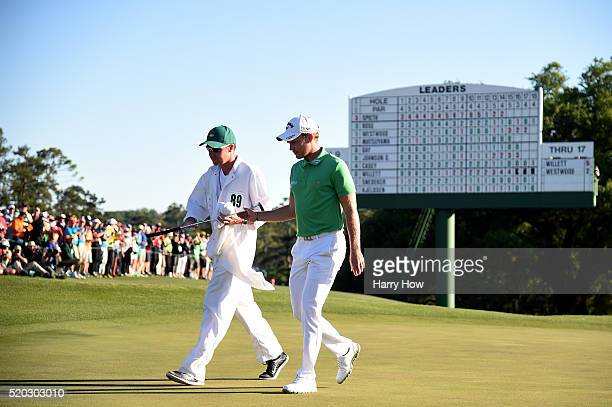 Danny Willett of England and caddie Jonathan Smart walk from the 18th green after finishing during the final round of the 2016 Masters Tournament at...