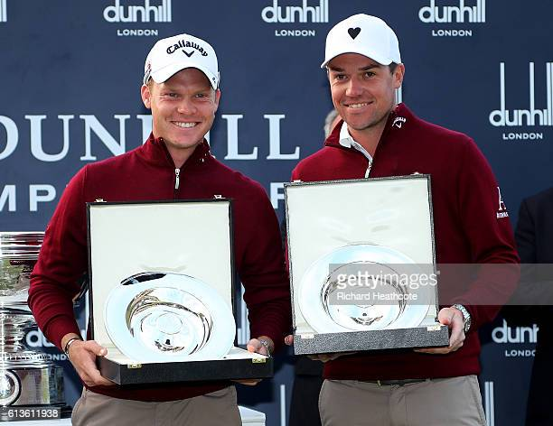 Danny Willett of England and his playing partner Jonathan Smart celebrate with their trophies on the 18th green after winning the team event at the...