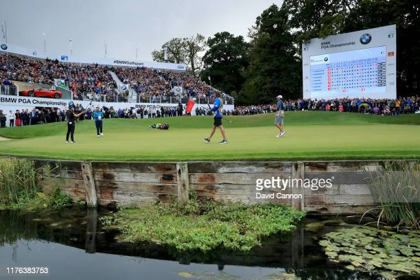Danny Willett of England celebrates after holing the winning putt on the 18th hole watched by his playing partner Jon Rahm of Spain during the final...