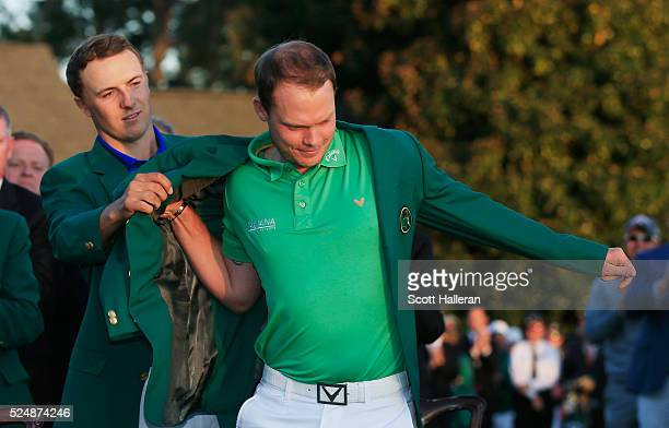 Danny Willett of England celebrates his victory as Jordan Spieth presents him the winner's green jacket after the final round of the 2016 Masters...