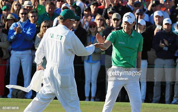 Danny Willett of England celebrates with his caddie on the 18th green during the final round of the 2016 Masters Tournament at the Augusta National...