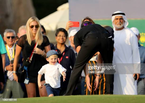 Danny Willett of England is greeted by his young son Zach on the 18th green as his wifer Nicole looks on after his two shot win during the final...