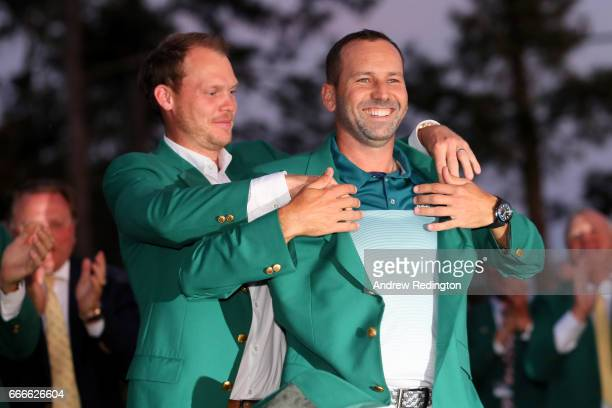 Danny Willett of England presents Sergio Garcia of Spain with the green jacket after Garcia won in a playoff during the final round of the 2017...