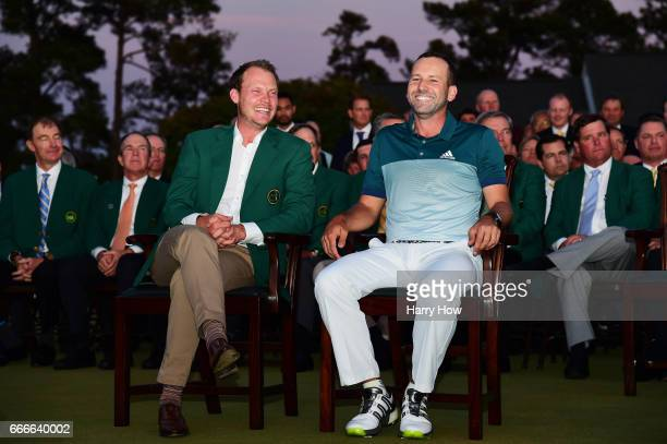 Danny Willett of England smiles alongside Sergio Garcia of Spain during the Green Jacket ceremony after Garcia won in a playoff during the final...