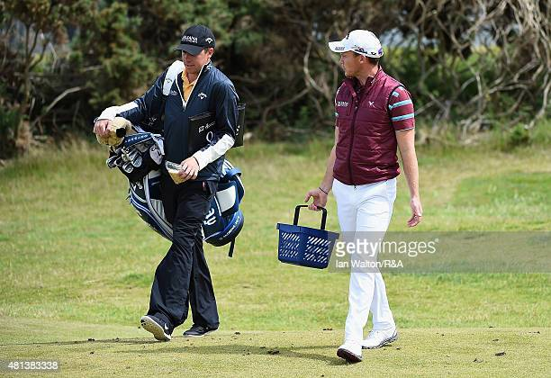 Danny Willett of England talks with his caddie Jonathan Smart on the practice range prior to competing in the final round of the 144th Open...