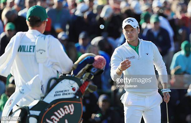 Danny Willett of England tosses his ball to his caddie on the 18th green during the final round of the 2016 Masters Tournament at the Augusta...