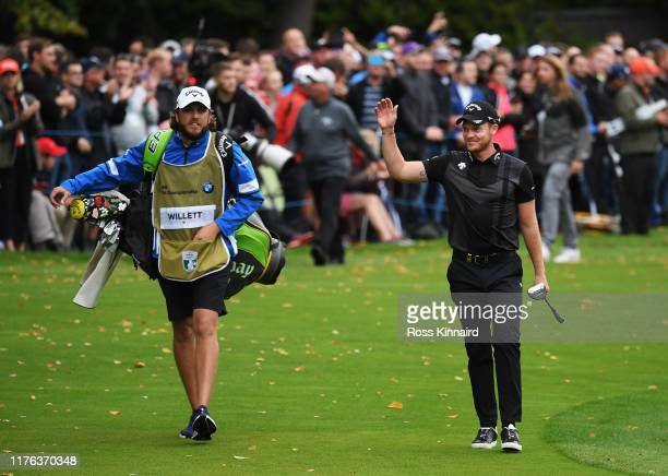 Danny Willett of England waves to the fans as he walks onto the 18th hole with his caddie Sam Haywood during Day Four of the BMW PGA Championship at...