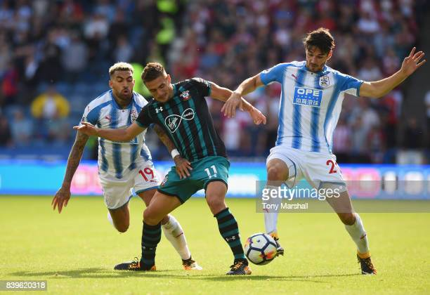 Danny Williams and Christopher Schindler of Huddersfield Town tackle Dusan Tadic of Southampton during the Premier League match between Huddersfield...