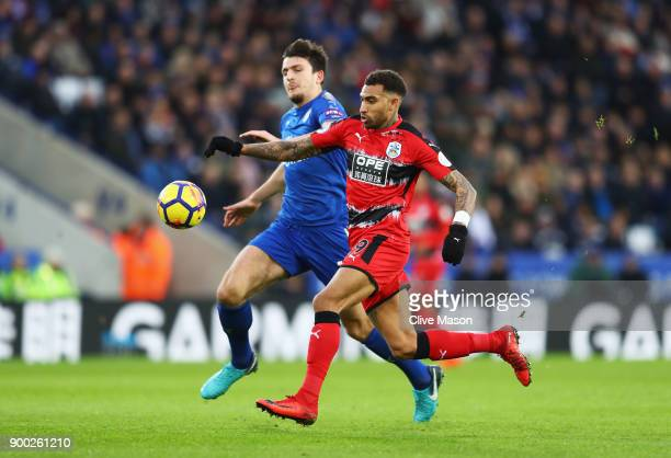 Danny Williams of Huddersfield Town is challenged by Harry Maguire of Leicester City during the Premier League match between Leicester City and...
