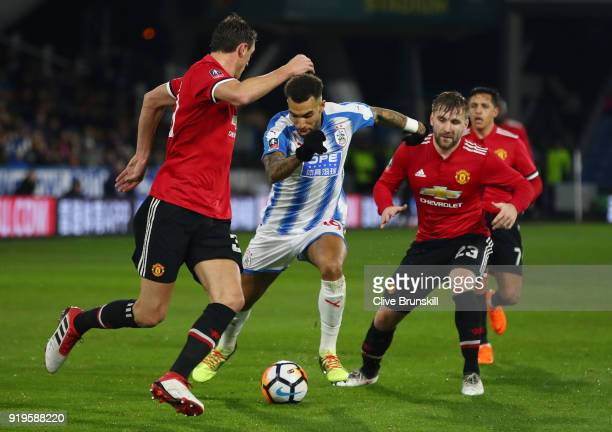 Danny Williams of Huddersfield Town runs with the ball under pressure from Nemanja Matic of Manchester United and Luke Shaw of Manchester United...