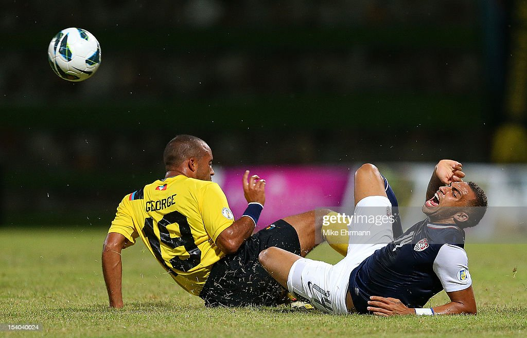 Danny Williams #14 of the United States dives for a ball against George Luke Anthony of Antigua and Barbuda during a World Cup Qualifying game at Sir Vivian Richards Stadium on October 12, 2012 in Antigua, Antigua and Barbuda.
