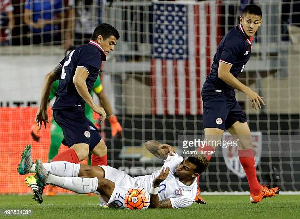 Danny Williams of the United States falls to the ground battling for the ball against Johnny Acosta of Costa Rica during the first half at Red Bull...
