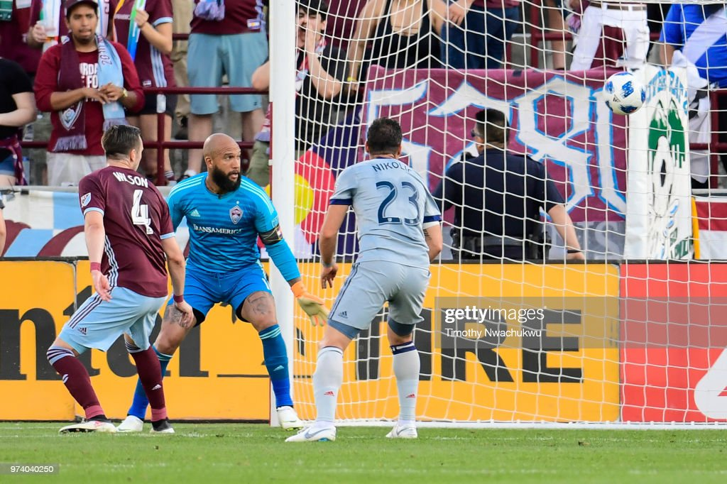 Danny Wilson #4 and Tim Howard #1 of Colorado Rapids and Nemanja Nikolic #23 of Chicago Fire watch as Wilson scores an own-goal at Dick's Sporting Goods Park on June 13, 2018 in Commerce City, Colorado.