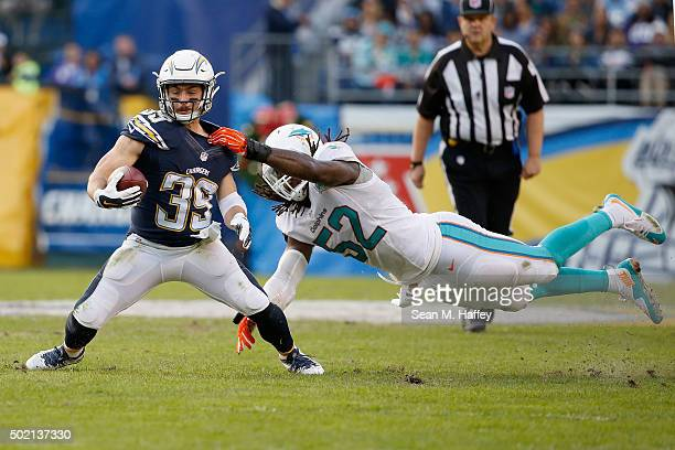 Danny Woodhead of the San Diego Chargers is tackled by middle linebacker Kelvin Sheppard of the Miami Dolphins during the second half of a game at...